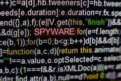 Macro photo of computer screen with program source code and highlighted SPYWARE inscription in the middle. Script on the Royalty Free Stock Photography