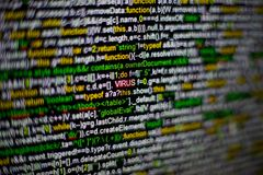 Macro photo of computer screen with program source code and highlighted VIRUS inscription in the middle. Script on the Royalty Free Stock Photography