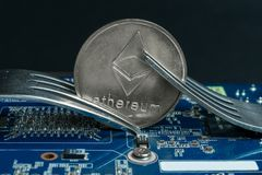 Cryptocurrency Ethereum ETH with a fork on the motherboard royalty free stock photography