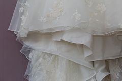 A macro photo of a detailed white wedding dress with white flowers and fake diamonds knitted to the dress. In europe Stock Photo