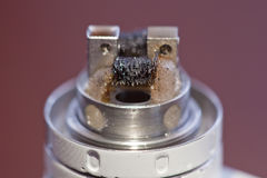 Macro photo of dirty twisted coil mounted in the electronic cigarette Royalty Free Stock Photography