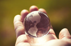 Macro photo of glass globe in human hand Royalty Free Stock Image