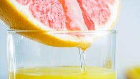 Macro image of grapefruit fresh juice flowing from freshly cut slice in glass stock images
