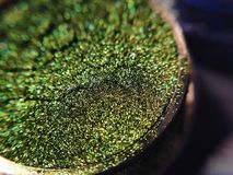Macro photo green eye shadow pigment glitter gloss cosmetic make up.  Stock Photo