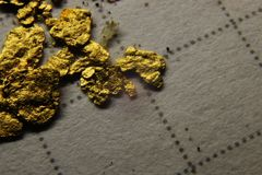 A macro photo of nuggets of gold on a paper royalty free stock images