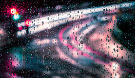 Macro photo or raindrops with trailing blurred red, pink, blue and green motion trail lights in the background Royalty Free Stock Photography