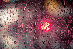 Macro photo or raindrops with trailing blurred red, pink, blue and green motion trail lights in the background Royalty Free Stock Images