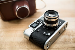 Macro photo of retro manual camera and leather case on table Royalty Free Stock Images