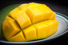 Macro photo of sliced mango on white plate Royalty Free Stock Photo