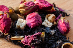 Macro photo of tea with a tea rose. The composition of the heap of tea roses and dried hibiscus flower located on a wooden Board. Stock Image