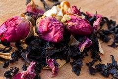 Macro photo of tea with a tea rose. The composition of the heap of tea roses and dried hibiscus flower located on a wooden Board. Stock Photo