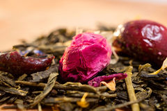 Macro photo of tea with a tea rose. The composition of the heap of tea roses and dried hibiscus flower located on a wooden Board. Royalty Free Stock Photography