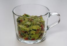 Chunky Homemade Guacamole in a Glass Cup. Macro photo of the texture of slightly guacamole served from a cup made of glass. Healthy and delicious food made of royalty free stock photos