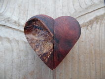 Macro Photograph of Handcrafted Little Wooden Heart. Macro photograph features a one of a kind, handcrafted wooden heart. Wood is in the background. Heart is Royalty Free Stock Images