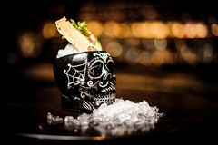 Macro photography of black skull-shaped glass filled with fresh and sweet summer cocktail. Among ice on the table stock photography