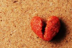 Macro photography of broken heart shaped of dog food wooden background royalty free stock images