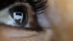 Macro photography. The eye of a woman who looks at the tablet. The screen of the tablet is reflected in the eyeball stock video