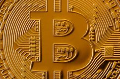 Macro photography of a golden yellow metal bitcoin. Close up shiny metal texture. Abstract business and modern technology backgro. Und. Cryptocurrency mining royalty free stock images