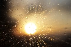 Macro photography of rain drops on the glass on a blurry background of the setting sun. Texture in dark and orange tones. Blur wit stock photo