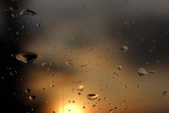 Macro photography of rain drops on the glass on a blurry background of the setting sun. Texture in dark and orange tones. Royalty Free Stock Photos