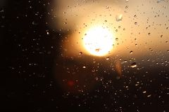Macro photography of rain drops on the glass on a blurry background of the setting sun. Texture in dark and orange tones. Stock Photo