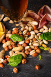Macro picture of pub appetizers next to a glass of beer. Mix of nuts decorated with basil leaves on a black background. Stock Images