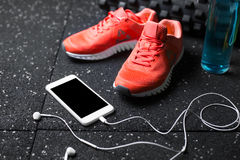 Macro picture of sports accessories for gym training. Bright training shoes, a smart phone, blue bottle on a floor royalty free stock images