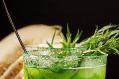 Macro picture of a tarragon drink. A glass of green alcoholic beverage. Cold herbal drink and sweet melon on a black background. royalty free stock photography