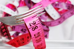 Macro pink tape measure on fork Royalty Free Stock Images