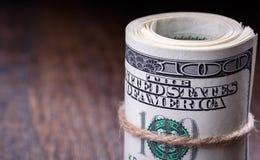 Macro, plan rapproché des billets de banque américains roulés du dollar du côté droit Fond en bois Image stock
