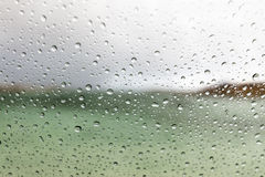 Macro raindrops on a car window. Raindrops hitting the window of a car while driving. Open nature landscape out off focus in the background Stock Photos