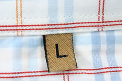 Macro reale del contrassegno dei vestiti - GRADUI la L secondo la misura fotografia stock libera da diritti