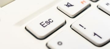 Macro recording of the escape character on a white laptop keyboard royalty free stock photos