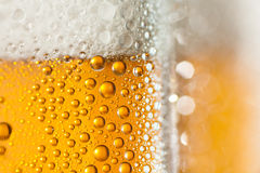 Macro of refreshing beer. Close-up of sweaty glass of beer royalty free stock photography