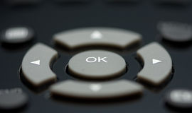 Macro of remote control buttons. Selective depth of focus to emphasize arrow and OK keys Stock Photo