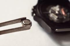 Macro of replacing a watch battery. With watchmaker tools watch battery replacement Royalty Free Stock Photography
