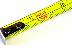 Macro of a retractable tape measure. Macro of an old yellow retractable tape measure Royalty Free Stock Images