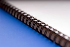 Macro of a ring bound document - on blue. Macro of a white spiral ring bound document - on a blue background stock image