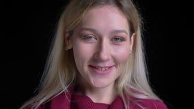 Macro ritratto del primo piano di giovane femmina caucasica affascinante che sorride allegramente e che posa davanti alla macchin archivi video