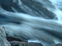 Macro of rocks by rushing water. Focus on rocks while water behind is blurred royalty free stock images
