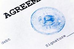 Macro Sello azul del bitcoin virtual de la moneda en un acuerdo de préstamo El acuerdo de préstamo, la firma se imprime en una ho Imágenes de archivo libres de regalías