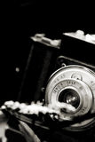 Macro shoot. A photo of an old classical Cmena film camera taking closeup shots of a flower in front of it stock images