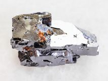 Galena crystal stone on white marble. Macro shooting of natural mineral rock specimen - Galena crystal stone on white marble background from Dalnegorsk in Stock Photography