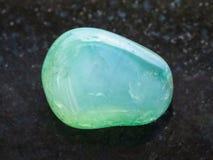 Polished green Calcite gemstone on dark background Stock Image