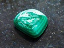 Polished Malachite gemstone on dark. Macro shooting of natural mineral rock specimen - polished Malachite gemstone on dark granite background royalty free stock photography