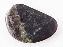 Polished olivinite stone on white. Macro shooting of natural mineral rock specimen - polished olivinite stone on white marble background from Kovdor region, Kola Royalty Free Stock Image