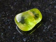 Polished Peridot gem stone on dark background Stock Photography