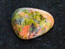 polished Unakite gemstone on dark background stock photo