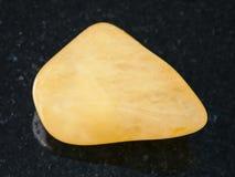 Polished yellow Aventurine gem stone on dark Stock Image
