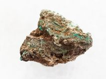 Raw Malachite (copper ore) stone on white marble. Macro shooting of natural mineral rock specimen - raw Malachite (copper ore) stone on white marble background stock image